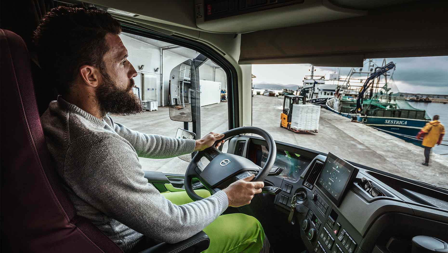 A driver in the cab of the new Volvo FH at a port